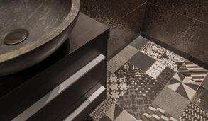 Mørkt bad med baderomsinnredning og mørke fliser med mønster