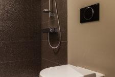Mønsterfliser på gulvet og brune vegger i dusjen