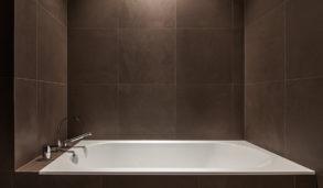 Mørkt bad med brune fliser og innfliset badekar