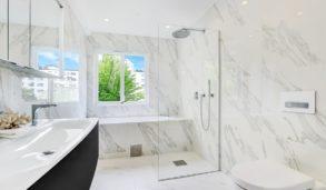 Innbygget badekar med marmorfliser og mosaikk i dusjen