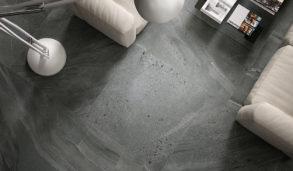 Grått gulv i stue med keramisk flis som ser ut som stein