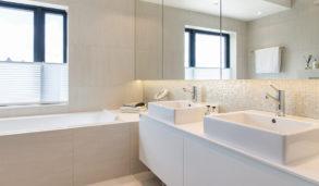 Bad med keramiske fliser og mosaikk bak servant, innbygget badekar