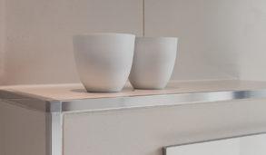 Minimalistisk bad med hvite fliser og hjørnelist