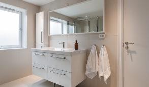 Minimalistisk bad med hvite fliser og hvit innredning