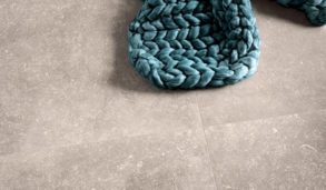 Varme grå gulvfliser med turkis heklet teppe