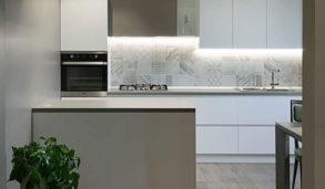 Hvitt kjøkken med lyse mønsterfliser i miks
