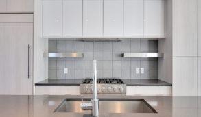 Hvitt kjøkken med mønsterfliser over benken og gasskomfyr