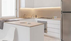 Hvitt kjøkken med tre benkeplate og beige fliser på gulv