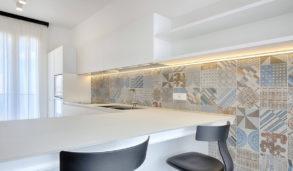 Hvitt kjøkken med stor flislagt vegg med mønster