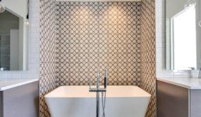 Vegg bak badekar flislagt med fliser med klassisk mønster