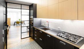 Mønstrede gulvfliser mot sort kjøkken og hvite vegger.