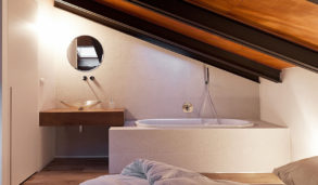 Lyst loftsbad med fliser med relieff og trebjelker i taket