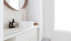 Hvitt bad med fliser som brettet papir og rundt speil