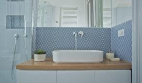 Blå mosaikkfliser i rombeform på vegg, hvit innredning