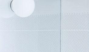 Detaljbilde av lyst bad med mønsterflis og veggmontert lys