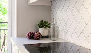 Rektangulære fliser lagt i fiskebensmønster på kjøkkenveggen