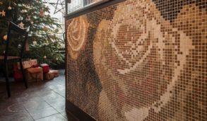 Glassmosaikk på vegg med rosemønster