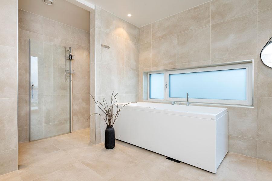 Lyst bad med beige fliser og badekar