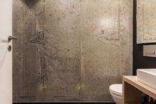 Røft bad med betongvegg og svarte fliser