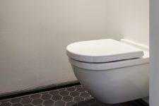 Lite toalett med svarte gulvfliser i hexagon