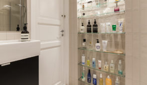 Jentebad med glasshyller og stående fliser på veggen