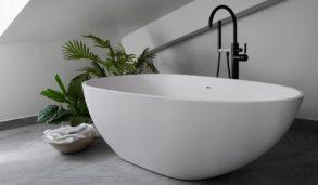Minimalistisk baderomsdesign med store grå fliser på gulvet. Ovalt badekar.