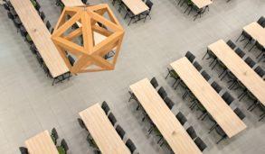 Store gulvfliser i kantine med grå fuge og sorte stoler