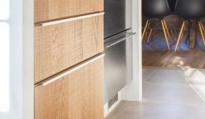 Kjøkkenfronter i tre og grå keramiske fliser på kjøkkengulvet