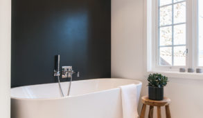Svart fondvegg bak badekaret og store gulvfliser med lys fuge