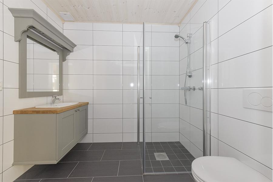 Enkelt bad med grå gulvfliser og hvite veggfliser