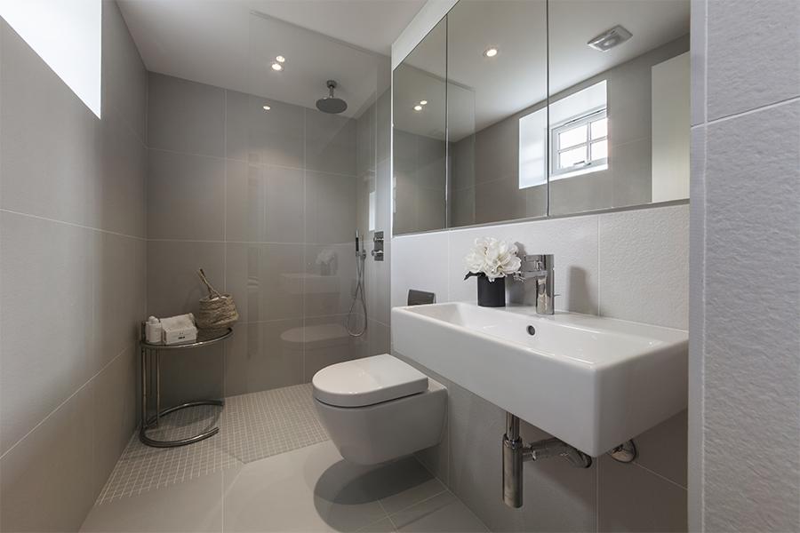 Store, ensfargede, grå fliser på gulv og vegg i minimalistisk bad