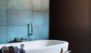 Mintfarget flis som fondvegg bak badekaret, mørke grå fliser på gulvet