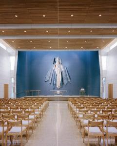Interiøret i kirken med stoler og alter med blå fliser