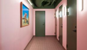 Korridor med rosa vegger og små fliser på gulvet