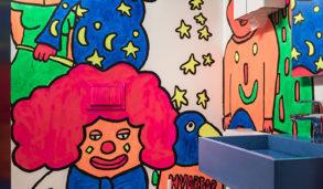 Toalett med barnetegning på veggen og cottofargede gulvfliser