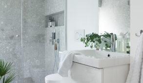 Minimalistisk bad med hvite vegegr og grå fliser
