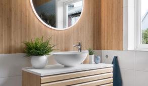 Baderomsinnredning med lyst treverk, hvite veggfliser og blå gulvfliser