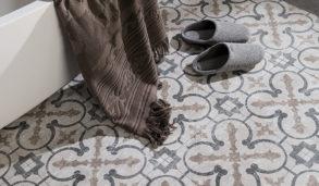 Stor mønstret gulvflis i naturtoner med badekar og håndkle