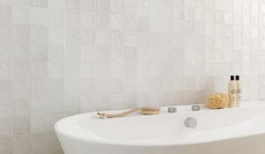 Frittstående badekar med lyse, klassiske fliser på veggen