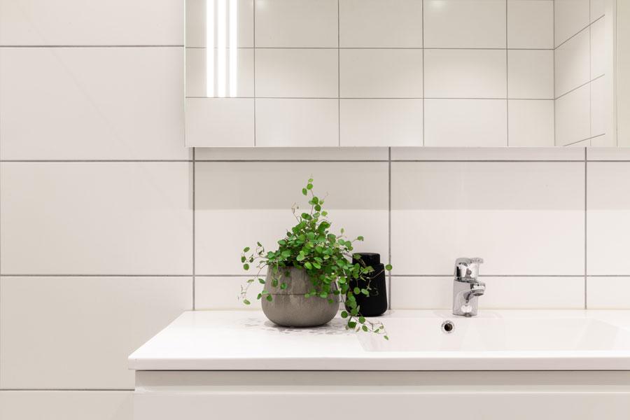 Enkle, hvite veggfliser med lys grå fug og hvit innredning