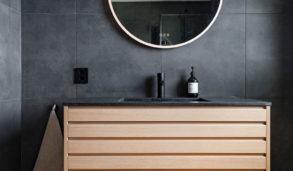 Mørke grå fliser på gulv og vegg med trefarget innredning