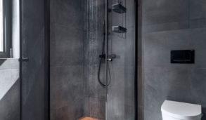 Mørkt bad med store fliser i grått