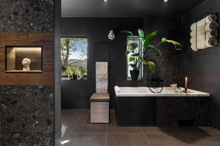 Bad i Porsgrunn med mørke fliser på gulv og vegg