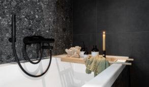Detaljbilde av badekar med mørke fliser og fondvegg