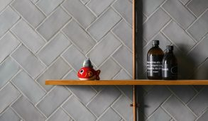 Små, grå veggfliser i fiskebeinsmønster på vegg