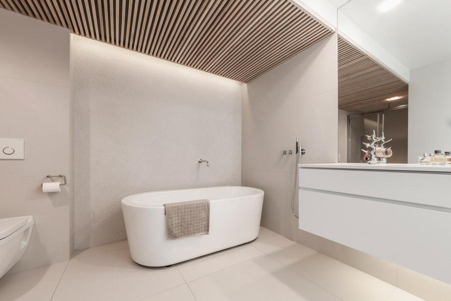 Lyst moderne bad med store fliser, spiletak og fondvegg