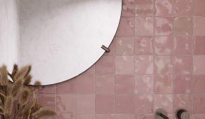 Rosa veggfliser på badet. Rundt speil og hvit servant.