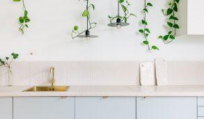 Lyseblått kjøkken med kremfarget flis på benk og bakvegg