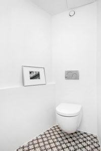 Enkelt toalett med mønsterflis på gulv